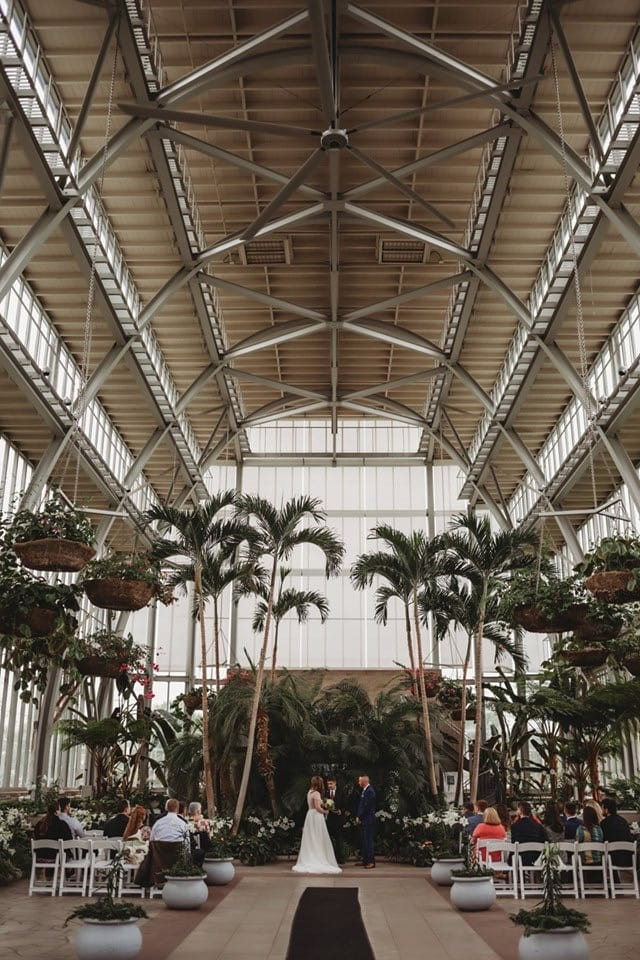Wedding Photography, couple getting married in a tall ceiling, open glass style vendor