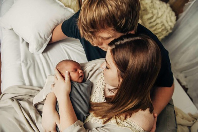 Newborn Photography, new parents looking down at baby