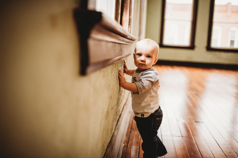 Children Photography, baby boy standing along the wall looking toward the camera