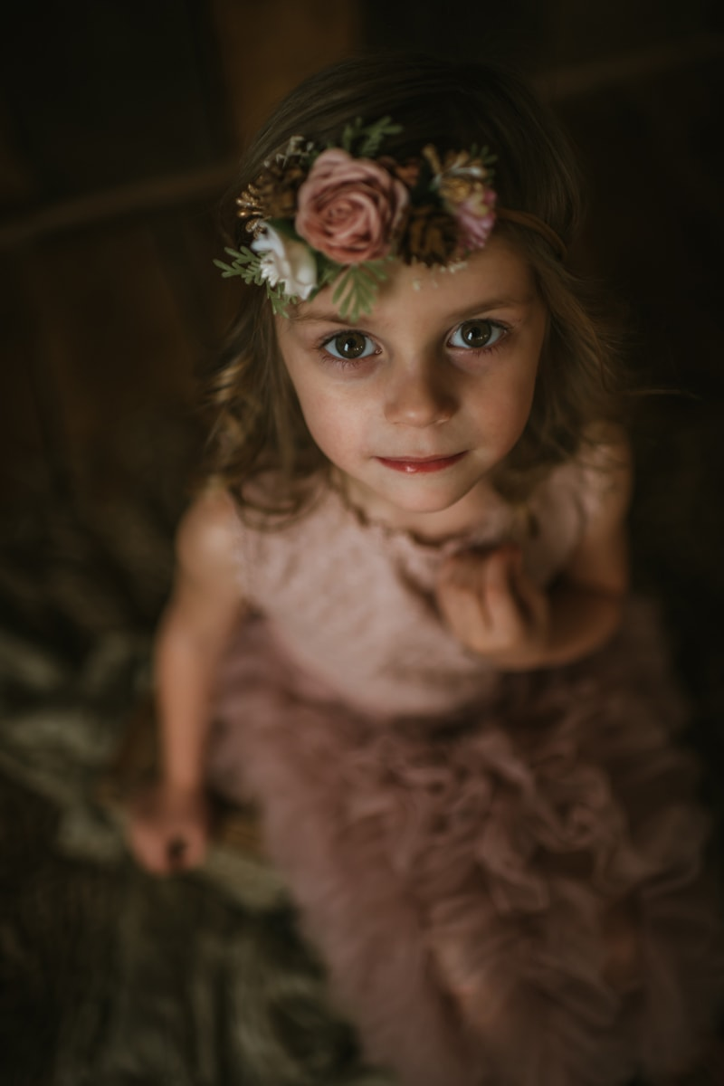 Children Photography, little girl with pink flower crown looking up at camera