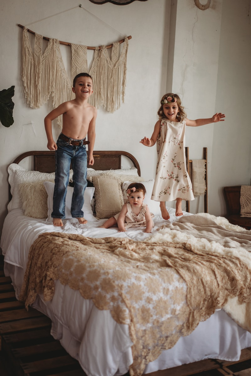 Children Photography, three siblings jumping on the bed together