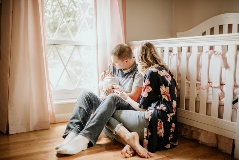 Newborn Photography, new parents sitting on the floor with baby in the nursery