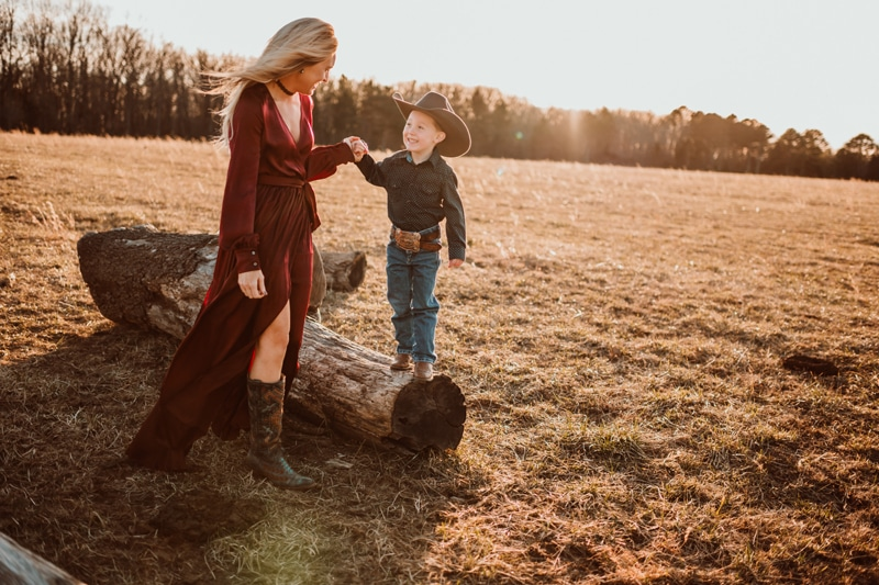 Family Photography, mother holding sons hand as he walks along a log