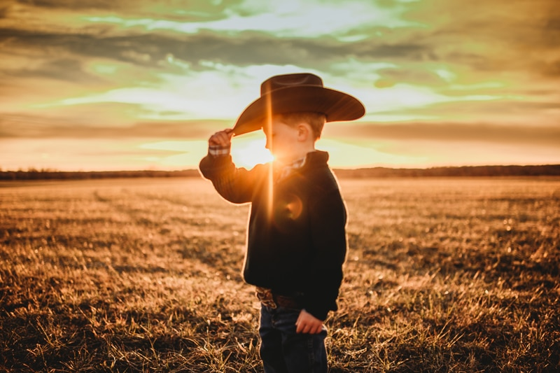 Children Photography, little boy tipping his cowboy hate with the sunset in the background