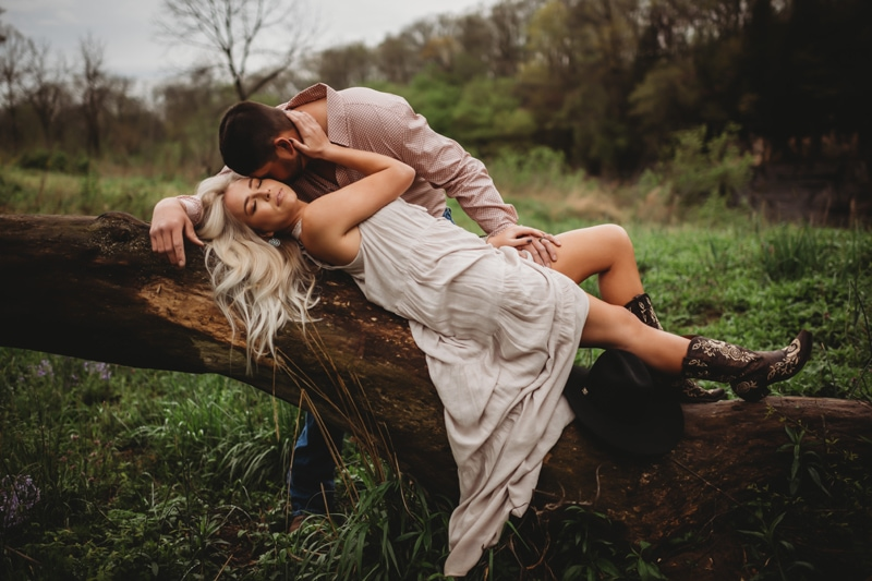 Couples Photography, woman laying on a large tree branch with man running his hand up her leg