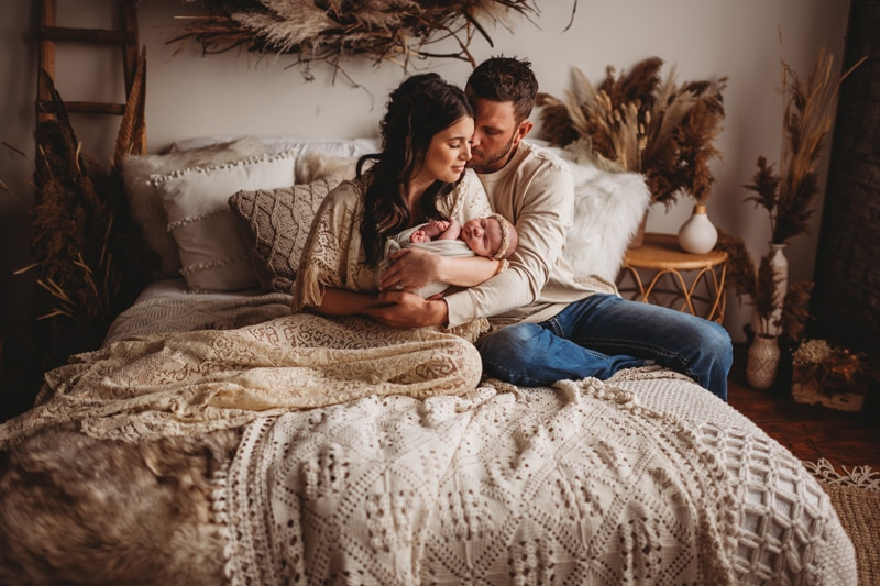 Newborn Photography, couple holding baby in the bed