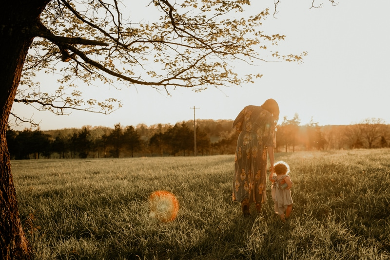 Family Photography, mother and child walking toward the sunset