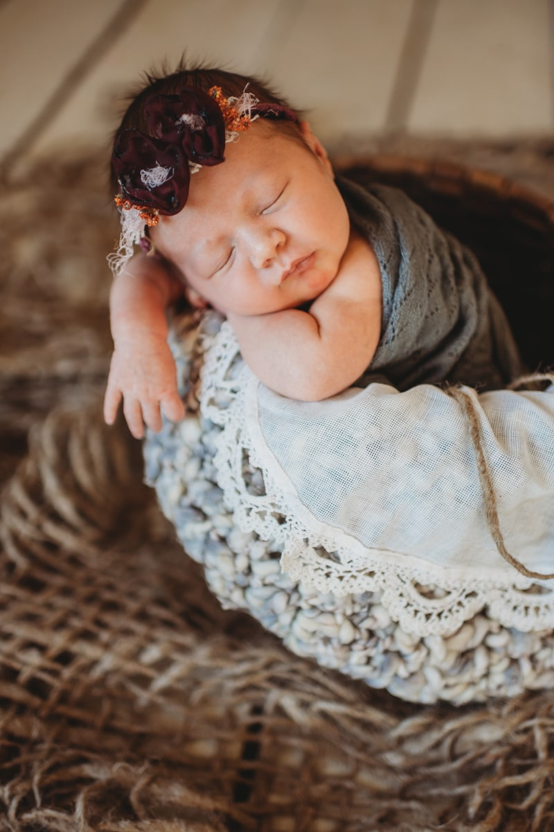 Newborn Photography, baby asleep in a basket with one arm sticking out