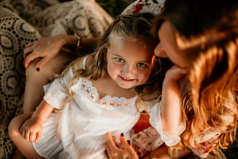 Family Photography, little girl sitting in mother's lap, looking up at camera