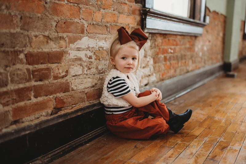 Children Photography, little girl sitting on the floor with big bow in her hair
