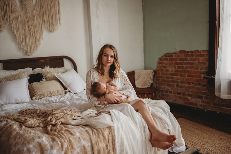 Family Photography, mother sitting on bed breastfeeding child