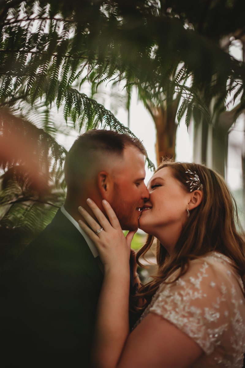 Wedding Photography, bride and groom kissing under ferns