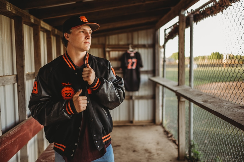 Senior Photography, boy standing in baseball dugout