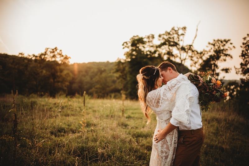 Wedding Photography, husband and wife kissing in a field