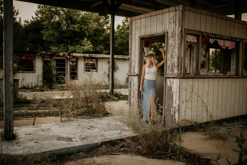 Senior Photography,  girl standing in the doorway of a dilapidated convenience store