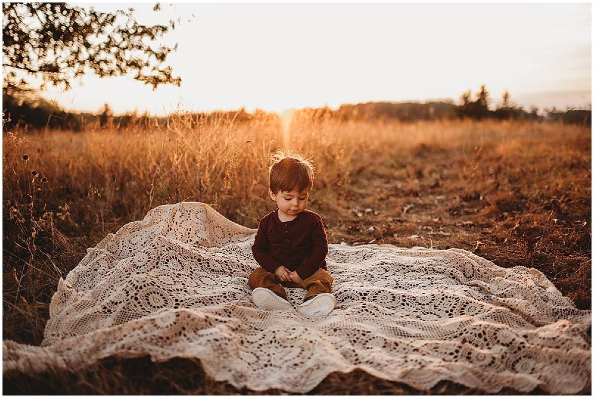 toddler boy sitting on blanket in field